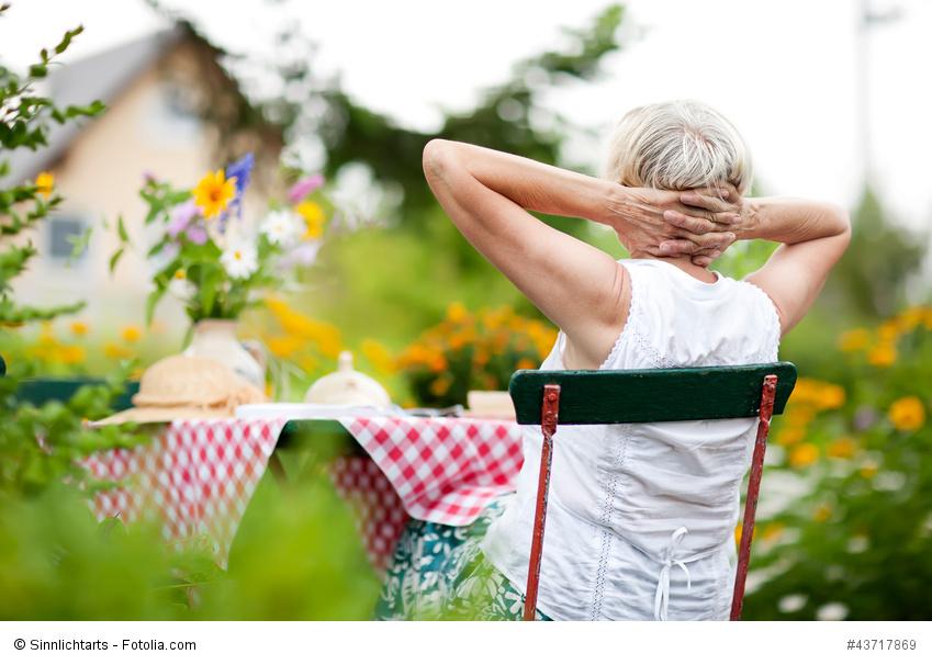 Deutschland, Seniorin auf Gartenstuhl mit verschränkten Händen hinter dem Kopf, entspannt sich in einem sommerlichen Garten.